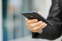 Бизнесмен держа Smartphone Phablet и наблюдая электронную почту Стоковая Фотография RF