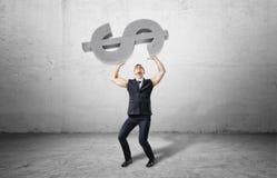 Бизнесмен держит большой объект доллара тяжелого бетона при рукави свернутые вверх Стоковая Фотография