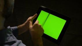 Бизнесмен держит зеленый ПК таблетки экрана в руке и быстром swiping на дисплее сток-видео