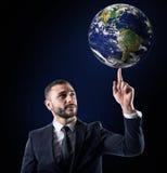 Бизнесмен держит мир с пальцем мир обеспеченный NASA Стоковые Фотографии RF