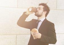 Бизнесмен есть и выпивая дальше для того чтобы пойти Стоковые Фото