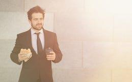 Бизнесмен есть и выпивая дальше для того чтобы пойти Стоковое Фото