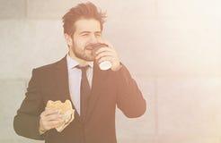 Бизнесмен есть и выпивая дальше для того чтобы пойти Стоковое Изображение RF