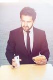 Бизнесмен есть и выпивая в кафе Стоковое Изображение RF