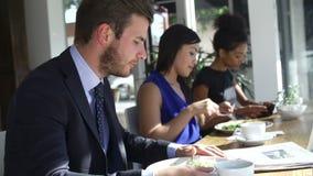 Бизнесмен есть обед и читая газету в Café видеоматериал