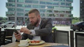 Бизнесмен есть обед и smartphone просматривать, steadicam видеоматериал