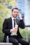 Бизнесмен есть сандвич для перерыв на ланч Стоковые Фото
