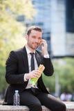 Бизнесмен есть сандвич для перерыв на ланч Стоковые Фотографии RF