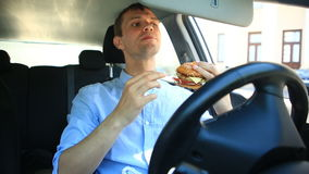 Бизнесмен есть фаст-фуд пока сидящ за рулем автомобиля Гамбургер