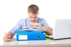 Бизнесмен детенышей перегружанный и сокрушанный в склонности стресса на отжатой папке офиса вымотанной и Стоковое Фото