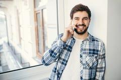 Бизнесмен детенышей усмехаясь итальянский говоря на сотовом телефоне Стоковое Изображение