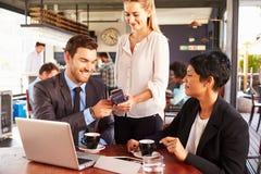 Бизнесмен делая безконтактную оплату карточки в кафе стоковая фотография