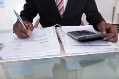Бизнесмен делая вычисления Стоковое Изображение