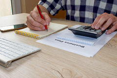Бизнесмен делая некоторую обработку документов используя его калькулятор Рука бизнесмена держа ручку шариковой авторучки работая  Стоковые Изображения