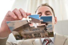 Бизнесмен делая дом головоломки Стоковые Изображения