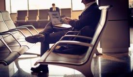 Бизнесмен ждать его самолет компьтер-книжка используя Стоковая Фотография
