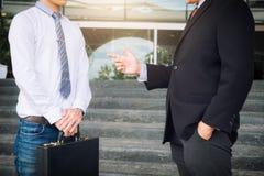 Бизнесмен заполняя черный портфель для того чтобы обменять дело перехода стоковые фото