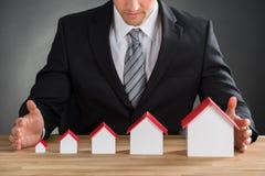 Бизнесмен защищая модели дома стоковые изображения rf