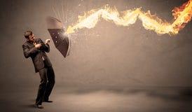 Бизнесмен защищая от огненной стрелы с зонтиком Стоковое Фото