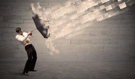 Бизнесмен защищая с зонтиком против ветра бумаг Стоковые Фотографии RF