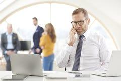 Бизнесмен звоня и используя компьтер-книжку на офисе Стоковое Фото