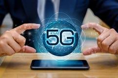 Бизнесмен земли телефона 5g соединяет всемирную руку кельнера держа пустую цифровую таблетку с умным и сетевое подключение 5G con стоковая фотография rf