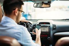 Бизнесмен игнорируя безопасность и отправляя СМС onmobile телефон пока управляющ Стоковое Фото