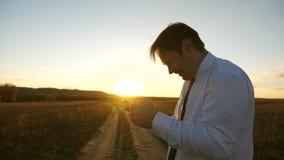 Бизнесмен играя игры планшета в парке в теплых лучах захода солнца человек играя игры на смартфоне t сток-видео
