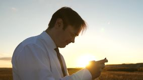 Бизнесмен играя игры планшета в парке в теплых лучах захода солнца человек играя игры на смартфоне t акции видеоматериалы