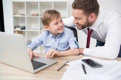 Бизнесмен играя на компьтер-книжке с его сыном Стоковые Фотографии RF