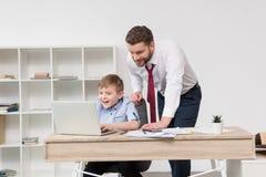 Бизнесмен играя на компьтер-книжке с его сыном Стоковое Фото