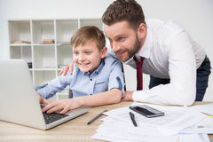 Бизнесмен играя на компьтер-книжке с его сыном Стоковые Фото