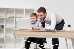 Бизнесмен играя на компьтер-книжке с его сыном Стоковое Изображение