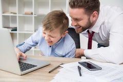 Бизнесмен играя на компьтер-книжке с его сыном Стоковая Фотография RF