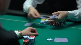 Бизнесмен играя покер на казино, получая карточки, шанс выиграть большие деньги видеоматериал