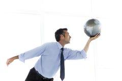 Бизнесмен играя с глобусом Стоковое Фото