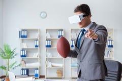 Бизнесмен играя футбол виртуальной реальности в офисе с VR g Стоковая Фотография