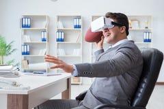 Бизнесмен играя футбол виртуальной реальности в офисе с VR g Стоковое Фото