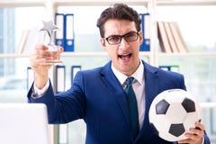Бизнесмен играя футбол в офисе Стоковая Фотография