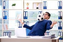 Бизнесмен играя футбол в офисе Стоковые Фотографии RF