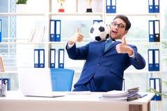 Бизнесмен играя футбол в офисе Стоковые Изображения RF