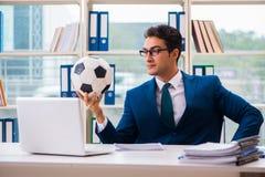 Бизнесмен играя футбол в офисе Стоковое Изображение