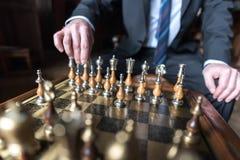 Бизнесмен играя шахмат Стоковые Изображения