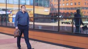 Бизнесмен идет около делового центра и говорит на телефоне HD акции видеоматериалы