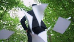 Бизнесмен идя в лес и бросая прочь все бумаги, наслаждаясь свободой сток-видео