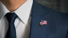 Бизнесмен идя к камере с государствами флага страны Pin-объединенными Америки сток-видео