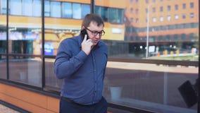 Бизнесмен идя около делового центра и говоря на телефоне акции видеоматериалы