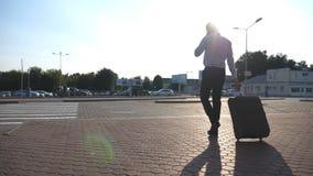 Бизнесмен идя от авиапорта ездить на такси автостоянка с его багажом и говоря на телефоне Идти молодого человека внешний и сток-видео