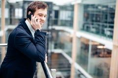 Бизнесмен идя пока говорящ на мобильном телефоне на его пути работать Стоковая Фотография RF