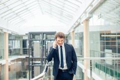 Бизнесмен идя пока говорящ на мобильном телефоне на его пути работать Стоковое Фото